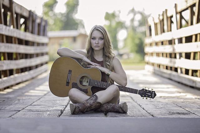 ギターを抱え道端に座る女性