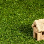 芝生の上に置かれた木製の家の模型